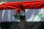 A Syrian protester makes a victory sign near their national flag during a protest calling for Syria's President Bashar al-Assad to step down, in front of the Syrian embassy in Amman