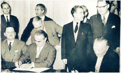 وزیر اقتصاد یونان در کنفرانس لندن در 1953 درحال امضای توافقنامهای که بر آن اساس 50 درصد بدهی آلمان بخشوده شد.