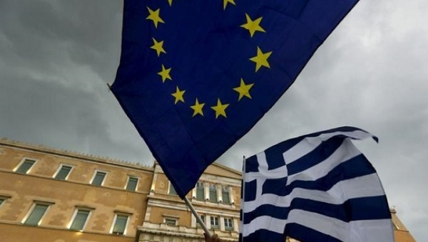 Protesters-wave-Greek-and-EU-flags-in-front-of-the-parliament-building-in-Athens-Greece-on-June-30-2015-Reuters